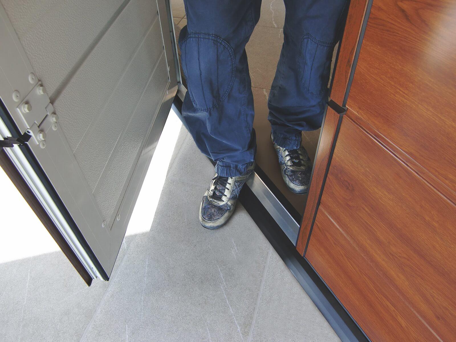Dettaglio porta pedonale a soglia ribassata simil legno